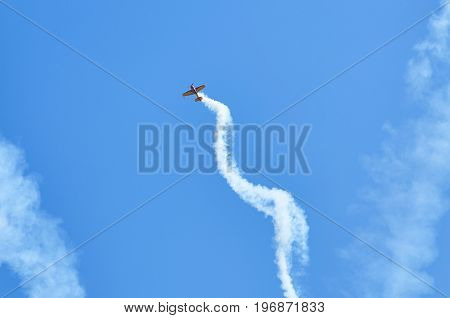 View on sport plane vapour trail in shape of spiral. White vapour trail track on blue sky background. Sport plane Aerobatic maneuver stunt. Spinning plane vapor trail in the sky. poster