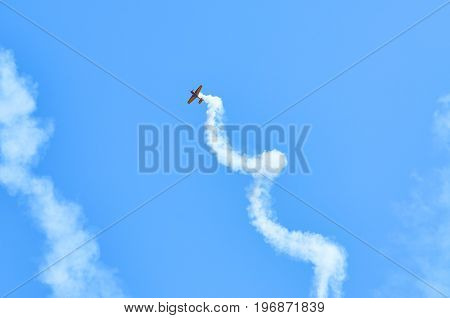 View on sport plane vapour trail in shape of spiral. White vapour trail track on blue sky background. Sport plane Aerobatic maneuver stunt. Spinning plane vapor trail in the sky.