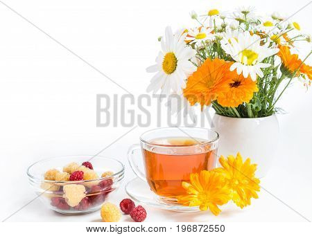 Tea with marigold, raspberry in a cup and bouquet in a vase on a white background.
