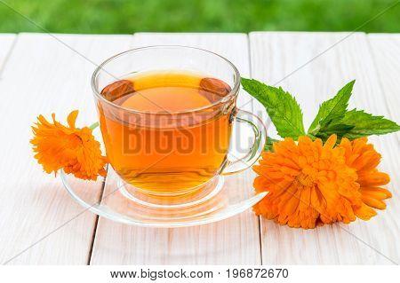 Calendula tea on a light wooden table.