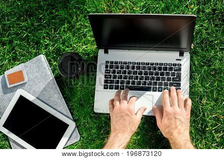 Close-up shot of handsome man's hands touching laptop computer's screen. Businessman using a laptop computer and sitting on the ground.