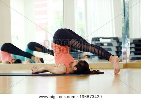 Asian woman practicing yoga fitness stretching flexibility pose working out healthy lifestyle wellness well being studio background
