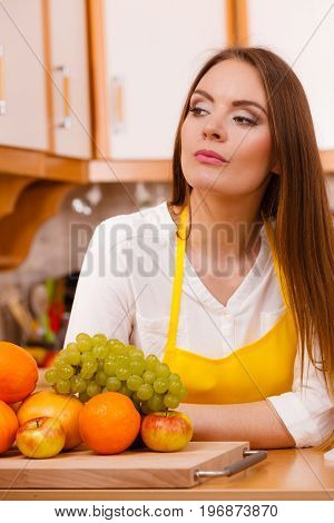 Fitness health fruits diet concept. Hungry lady eating. Young gorgeous female cook in kitchen preparing healthy food.