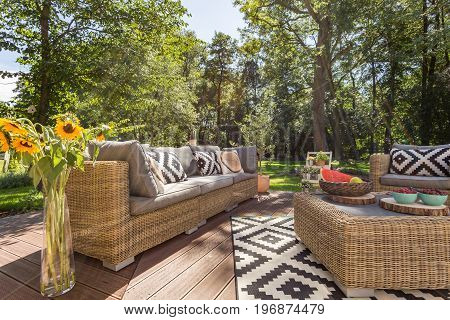 Cosy house veranda with garden furniture in a sunny day