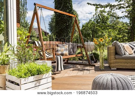 Shot of a wooden garden swing in a house terrace full of plants and flowers