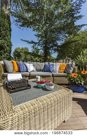 Cosy terrace with the typewriter on a coffee table and garden sofa with colourful pillows on