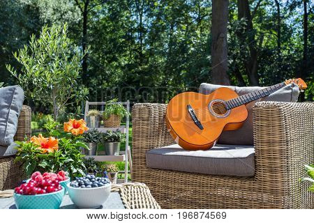 Shot of a wicker garden armchair with the guitar on