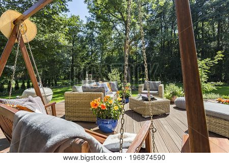 Comfortable house veranda with the wicker furniture and view of a garden in a summertime