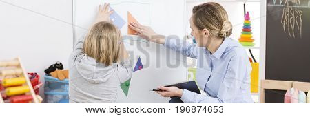 Young professional teacher finding an autism in her young student