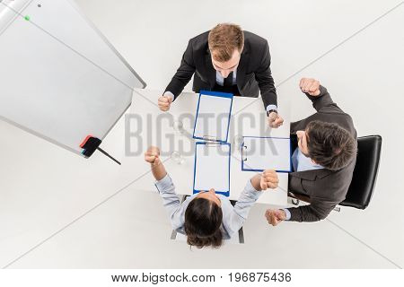 Overhead View Of Excited Business People Celebrating Triumph During Discussion At Meeting Isolated O