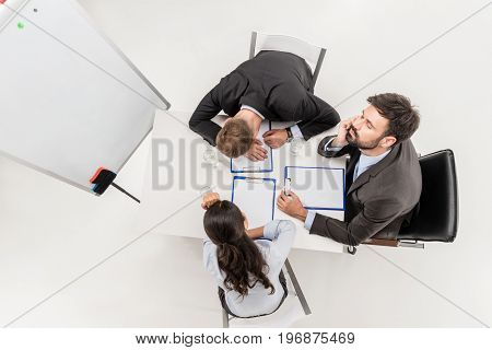 Overhead View Of Tired Business People Sitting At Workplace During Meeting Isolated On White