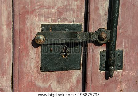 Close-up of iron bolt and lock on wooden door in Paraty, an amazing and historic town totally preserved in the coast of the Rio de Janeiro State, southwestern Brazil