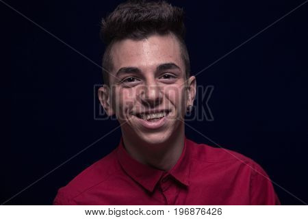 One Teenager Boy, Red Shirt, Caucasian, Dark Background, Looking To Camera, Smiling