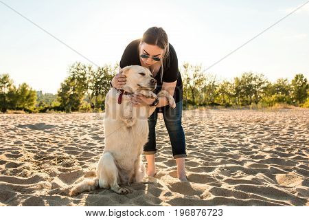Young female training labrador retriever dog on the beach at sunset. White labrador retriever with a young woman