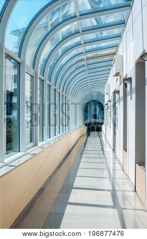 The corridor in the form of a semicircular tunnel with transparent glass walls. The horizontal frame.