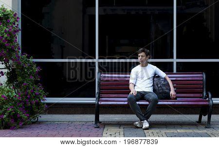 Serious teenager sitting on a bench on a black glass wall background
