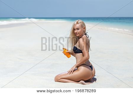 Beautiful blonde woman in the black bikini sitting with the bottle of sunscreen cream on the lonely beach with turquoise water and white sand. Zanzibar. Nungwi.