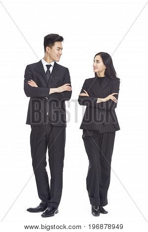 studio portrait of young asian business man and woman arms crossed looking at each other smiling isolated on white background.
