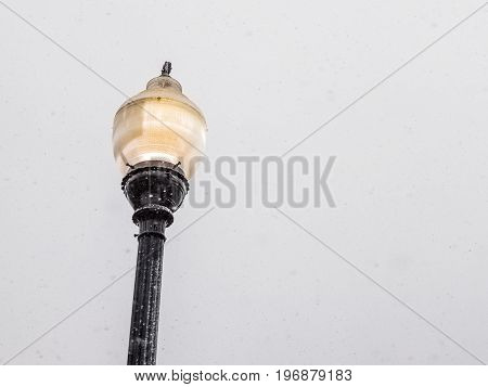 Isolated Yellow Lamp Post Lantern During Winter Snow