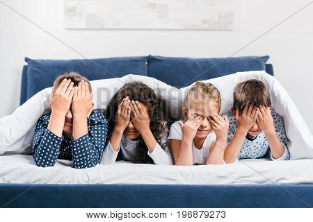 Obscured View Of Multicultural Children Covering Eyes While Lying In Bed Under Blanket At Home