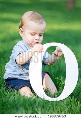 baby boy playing with big white letter O on green grass