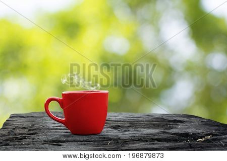 Hot drink in a red cup on grunge wood and Green bokeh blurred background