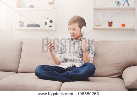 Excited teenage boy with braces playing football game on smartphone and listening to music in headphones, enjoying win while sitting on sofa in living room at home