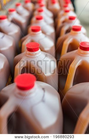 Rows Of Plastic Gallon Jars Filled With Apple Cider