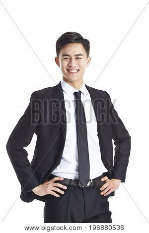 studio portrait of a young asian businessman in formal wear arms akimbo isolated on white background.