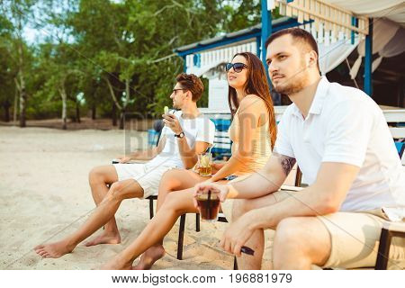 Lifestyle Young people enjoying summer vacation sunbathing drinking at beach bar. Two guys and a young girl sit on the terrace of the summer bar and enjoy the conversation