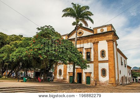 Paraty, Brazil - January 26, 2015. Old colored church, garden and cobblestone street in Paraty, a historic town totally preserved in the coast of the Rio de Janeiro State, southwestern Brazil