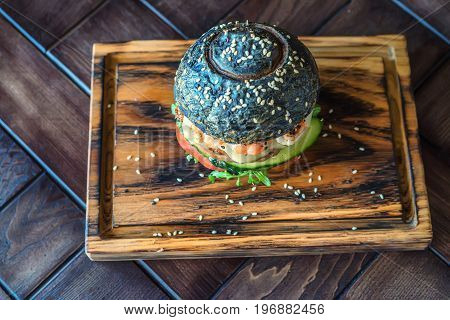 Close up delicious black burger with shrimps on wooden board in restaurant