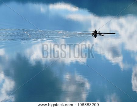 rower skims the water that reflects the sky and appears to be in clouds