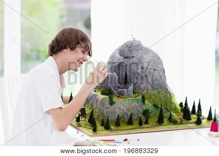 Teenager working on model building school project. Kids build miniature scale model mountain for geography class in high school. Extracurricular activities and hobby club. Art and crafts for child.
