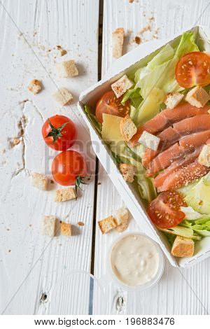 Close up top view Caesar salad with fish in box with cherry tomatoes, croutons and white sauce