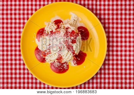 Top view of homemade spaghetti ice cream with red strawberry sauce and white chocolate on a plate