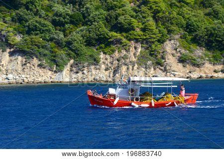 SKIATHOS GREECE, July 19 2017: Little red fishing boat near Skiathos island - Greece