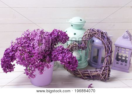 Fresh lilac flowers decorative violet heart and brigh lanterns on white wooden background. Selective focus. Still life.
