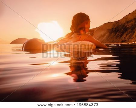 Beautiful woman swimming on the inflatable donut in the sea at warm summer sunset. Slim lady relaxing on her holidays at ocean