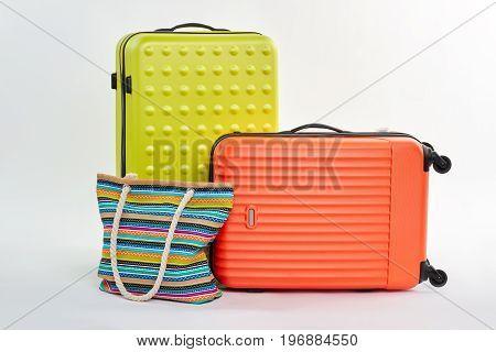 Modern suitcases and textile handbag. Traveler valises for south departure.