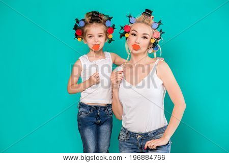 Funny family on a background of bright blue wall. Mother and her daughter girl with a paper accessories. Mom and child are holding paper lips on stick.