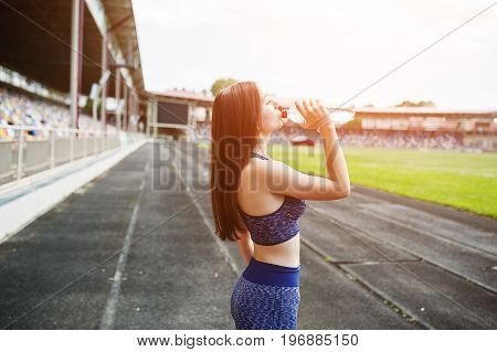 Portrait Of A Fit Woman Drinking Water After Running In The Stadium.