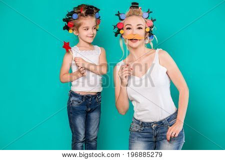 Funny family on a background of bright blue wall. Mother and her daughter girl with a paper accessories. Mom and child are holding paper star and mustache on stick.