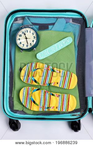 Open suitcase, alarm clock, flips. Bag of tourist with clothes.