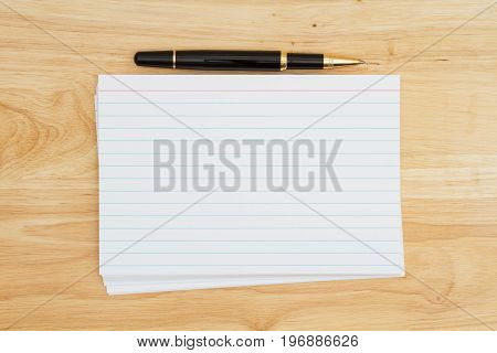 Stack of blank white index cards on wood desk and a pen with copy space for your message