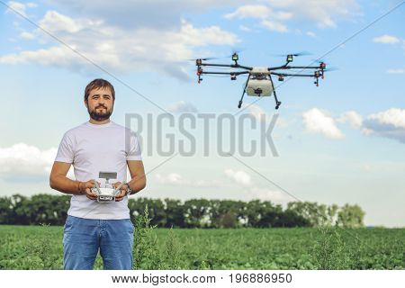Portrait of a young male farmer with a professional drone against a green field background. Agriculture drone flying with blue sky.
