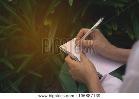 Woman sitting and holding a blue pencil and doing an exam
