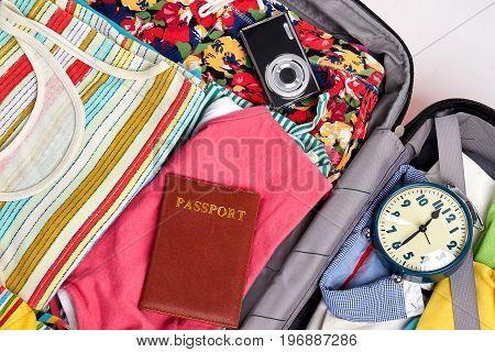 Things for sea abroad. Beach clothes, passport, camera, alarm clock in opened suitcase.