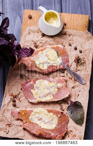 some peace of raw meat with sauce and basil on wooden plate