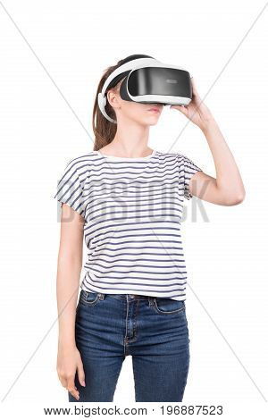 Beautiful young woman in a virtual glasses. Digital VR device. Female action in virtual reality helmet isolated on a white background. 3d vision technology, video game simulation. New audio equipment.